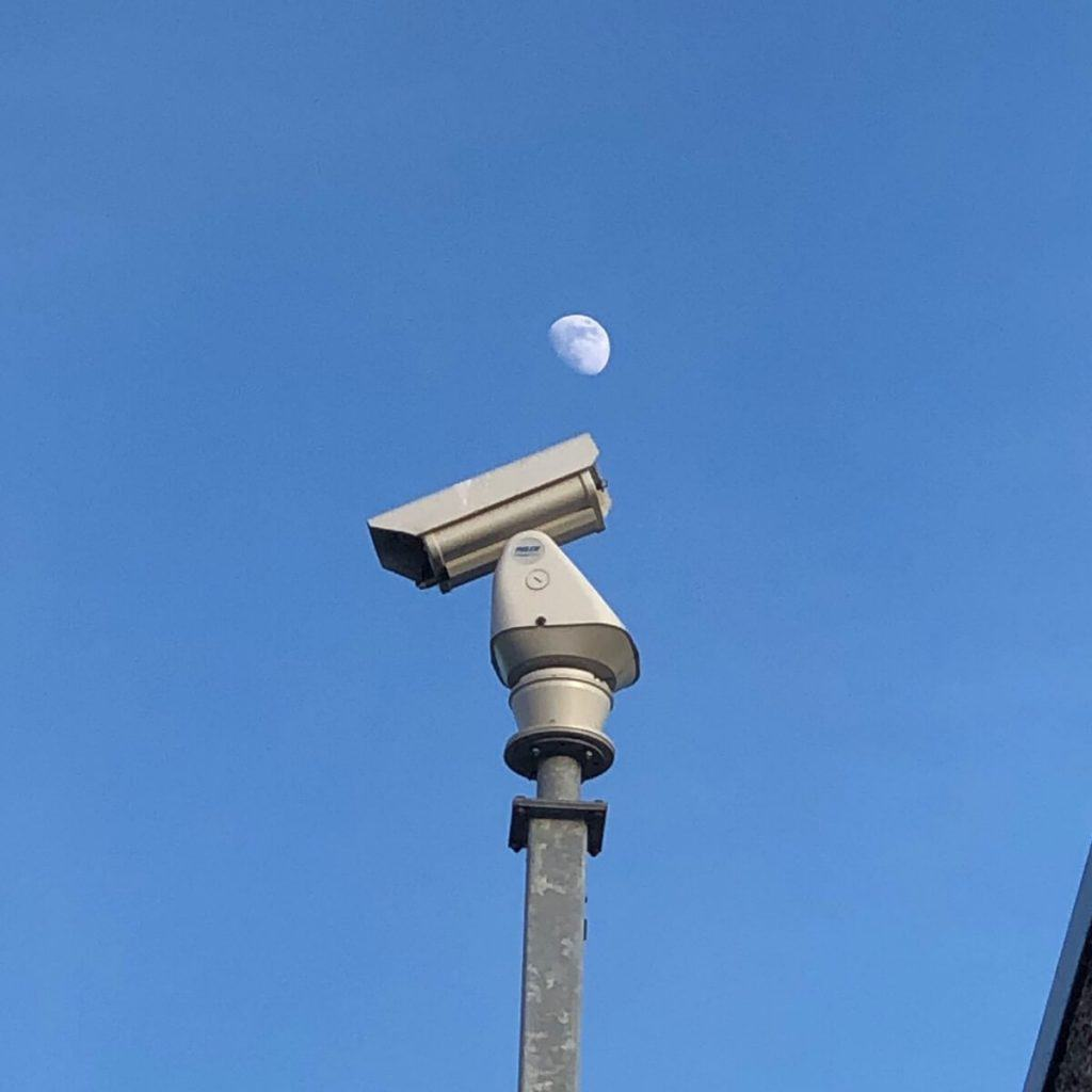 The moon above a surveillance camera